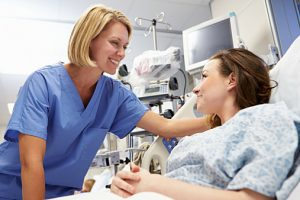 Young Female Patient Talking To Nurse In Emergency Room