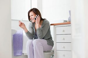 Woman on cell phone with pregnancy test