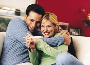 Couple Embracing After Looking at Pregnancy Test